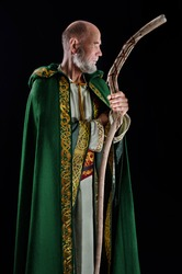 old wizard dressed in a green cloak with a hood. He holds his magic staff in his hands.