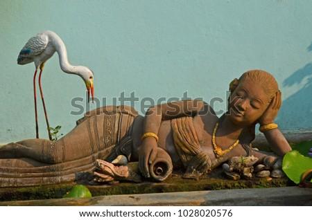 Old woman and egret bird sculptures beside blue wall - Shutterstock ID 1028020576