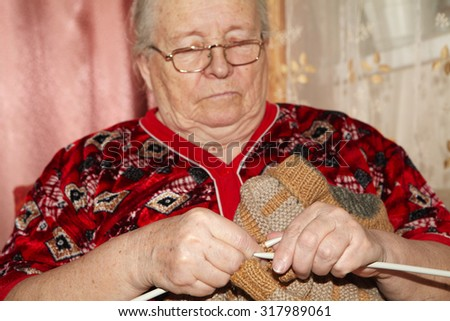 Old woman and knitting sweater. Senior people