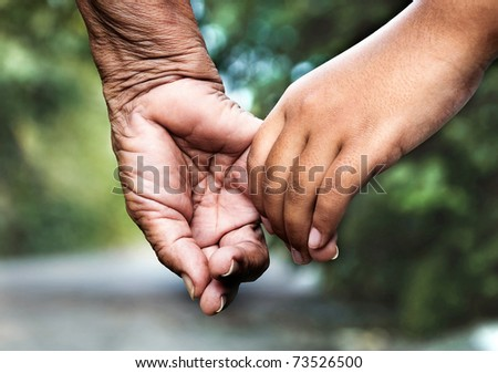 stock photo : Old woman and young girl holding hands together