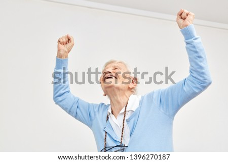 Old woman cheers with clenched fists as a sign of vitality and courage