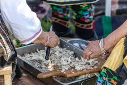 Old woman deboning chicken meat for traditional bulgarian soup called Kurban.