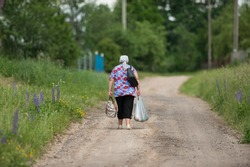 old woman drags heavy bags along the road