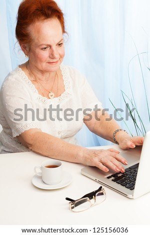 Old woman drinking coffee and reading morning news from laptop