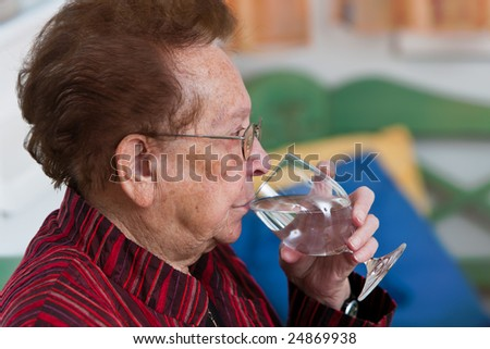 Old woman drinking water from a glass