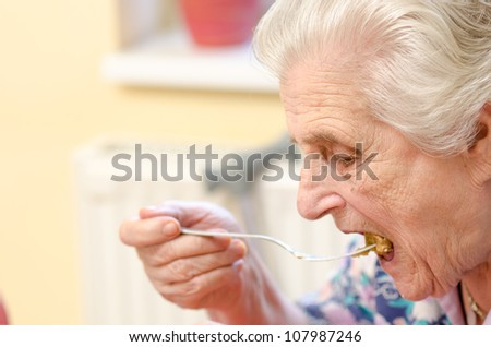 Old woman eating soup