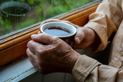 Old woman hands holding cup of tea near window with raindrops. Melancholic mood