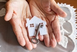Old woman holding  house model and house key in hand.Mortgage loan approval home loan and insurance concept