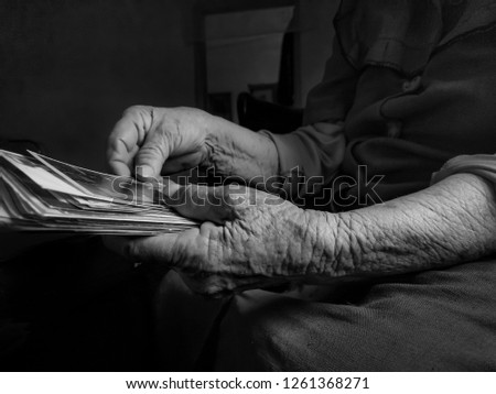 Old woman holding picture in hand. black and white