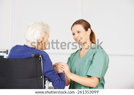 Old woman in a wheelchair as patient with geriatric nurse in a nursing home