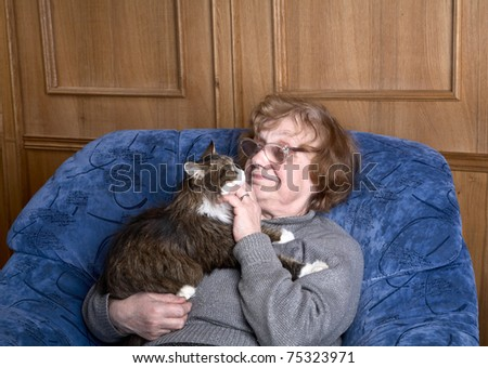 old woman in an armchair with a cat on hands