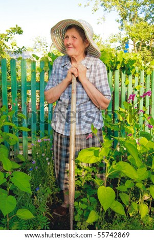 old woman in hat working in the garden