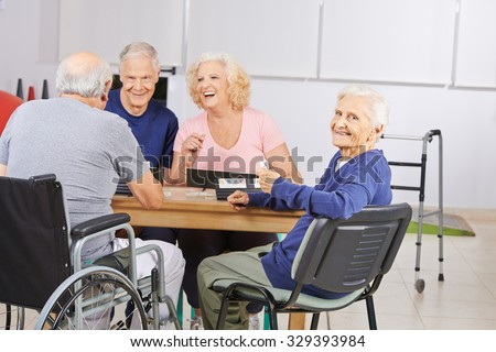 Old woman in nursing home playing with laughing senior people
