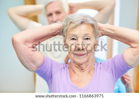 Old woman in physiotherapy is doing healthy exercise in back gymnastics