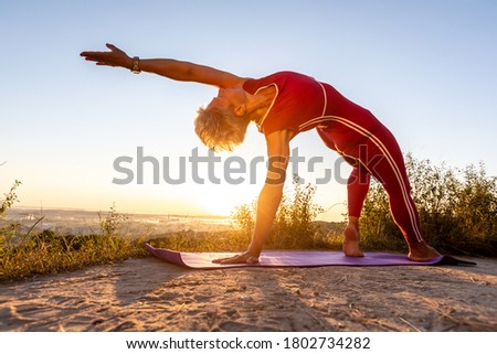 Old Woman in red Tracksuit doing Wheel half Moon power Pose lift up one hand in the sunrise