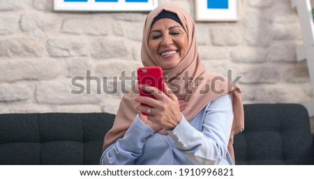 Old woman in turban is having a video conversation with her mobile phone in slow motion. The old woman with a turban is having a video chat with her loved ones at home. Stockfoto ©