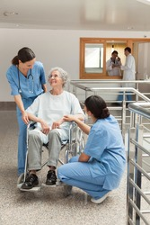 Old woman in wheelchair talking with nurses in hospital corridor. Healthcare workers in the Coronavirus Covid19 pandemic