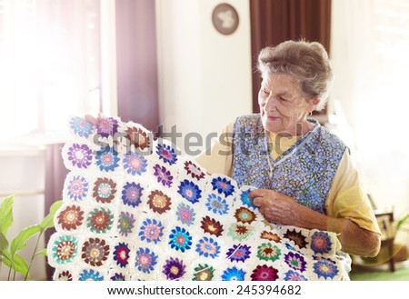 Old woman is knitting a blanket inside in her living room #245394682