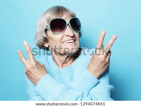 Old woman laugh and showing peace or victory signat camera. Emotion and feelings. Portrait of expressive grandmother.Close up. #1294074841