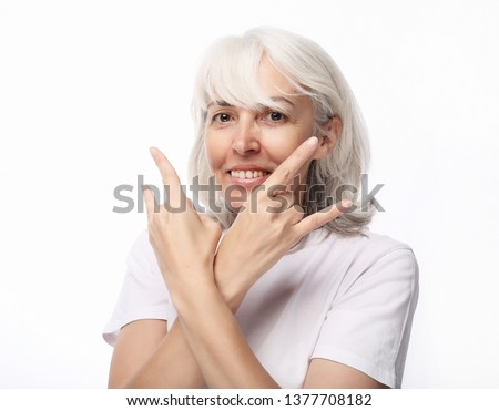 Old woman laugh and showing peace or victory signat camera. Emotion and feelings. Portrait of expressive grandmother. #1377708182