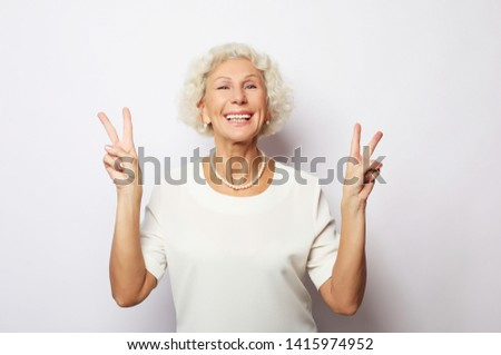 Old woman laugh and showing peace or victory signat camera. Emotion and feelings. Portrait of expressive grandmother. #1415974952