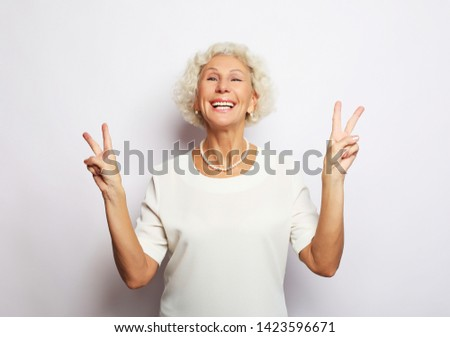 Old woman laugh and showing peace or victory signat camera. Emotion and feelings. Portrait of expressive grandmother. #1423596671