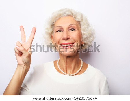 Old woman laugh and showing peace or victory signat camera. Emotion and feelings. Portrait of expressive grandmother. #1423596674