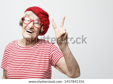 Old woman laugh and showing peace or victory signat camera. Emotion and feelings. Portrait of expressive grandmother.Close up. #1457841356
