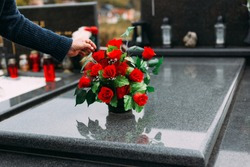 Old woman laying down bouquet of artificial flower on a grave