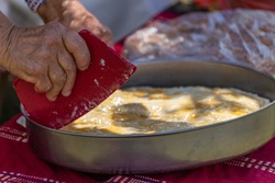 Old woman making traditional bulgarian pie with white cheese called banitsa. Cutting the pieces with old tool.
