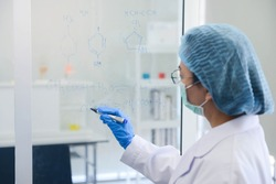 Old woman medical research scientist is write down the chemical formula on the glass board