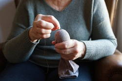 Old woman mending a sock at home