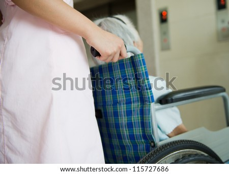 old woman on a wheelchair with assistant