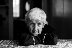 Old woman portrait in dark room, black and white photo.