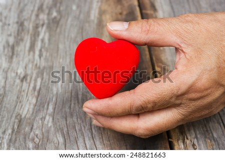 Old woman's hand holding  a red heart shape. On wooden background. #248821663