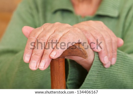 Old woman's hands resting on the walking stick