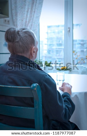 Old woman sitting alone at her kithchen table with a glass of water looking out of the window, blue filter effect, concept of old-age depression, loneliness #1187977087