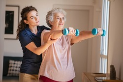Old woman training with physiotherapist using dumbbells at home. Therapist assisting senior woman with exercises in nursing home. Elderly patient using dumbbells with outstretched arms.