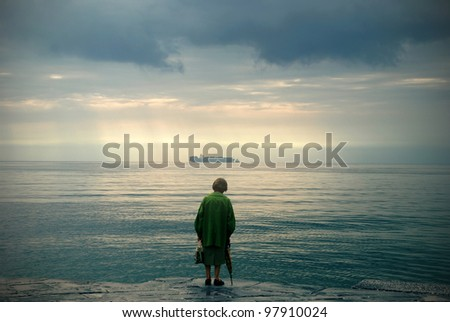 Old woman watching the sea