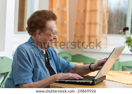Old woman with a laptop writes e-mail