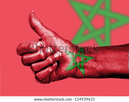 Old woman with arthritis giving the thumbs up sign, wrapped in flag pattern, Morocco