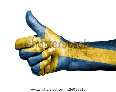Old woman with arthritis giving the thumbs up sign, wrapped in flag pattern, Sweden