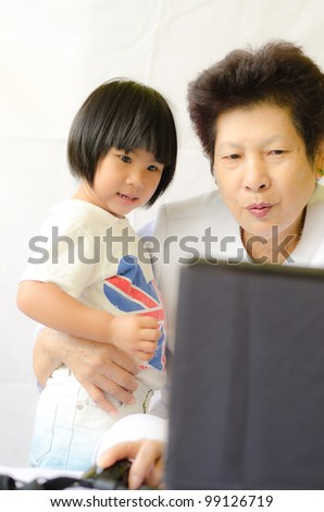 Old woman with girl using laptop computer