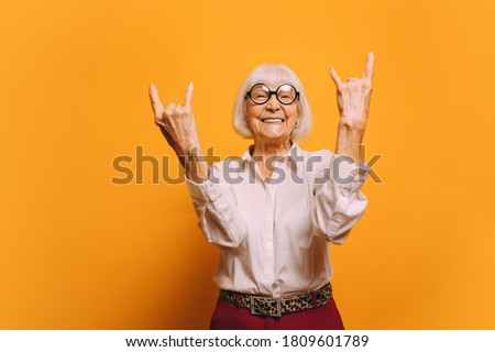 Old woman with white hair with round glasses wearing white blouse, red pants and leopard print belt standing isolated over orange background. Sign of the horns