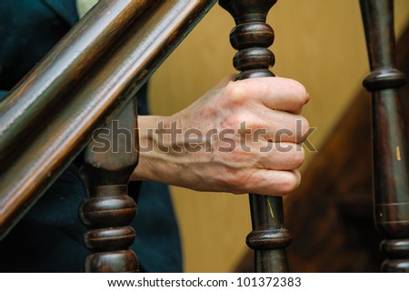 old woman wrinkled hands holding of handrail