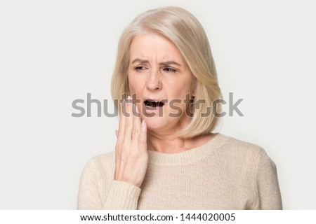 Old woman yawn cover mouth with hand being bored. Elderly female feeling exhausted, sleepy, tired, overworked, no energy headshot. Lady in years gaping portrait at studio isolated on grey background ストックフォト ©