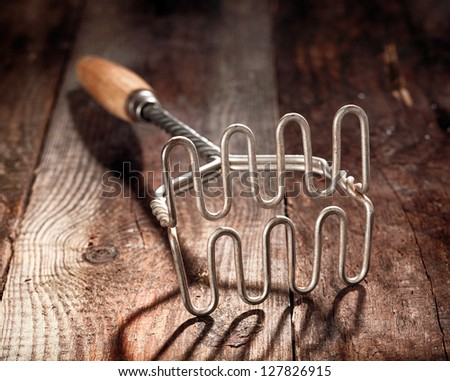 Old wood and metal potato masher on a textured wooden surface with shallow dof and focus to the steel wire grid at the end