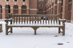 Old wood bench with red brick building as a background under a heavy snow storm