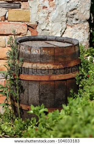 Old wood cask in front of a brick wall