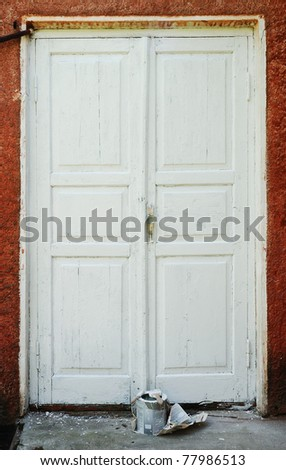 Old wood door is peeling away. There are tin of paint and brush in front of it. It is in need of repair.
